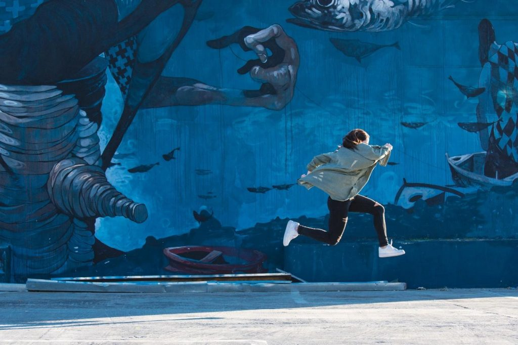 Young person running and jumping against a backdrop of street art.