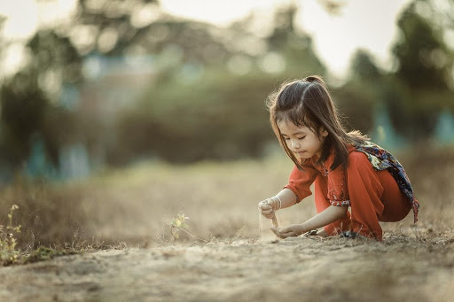 Photograph of a little girl playing in sandy soil.