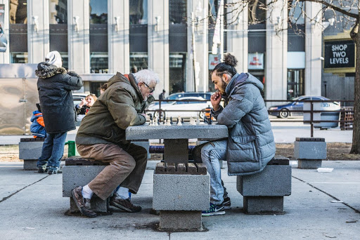 An older man and younger man playing chess outside in front of a building